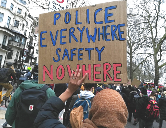 A woman of colour wearing a headscarf holds up a placard: Police everywhere, safety nowhere.  She is among a crowd of protesters.